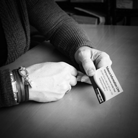 Hands holding a Tobacco Information Line card.