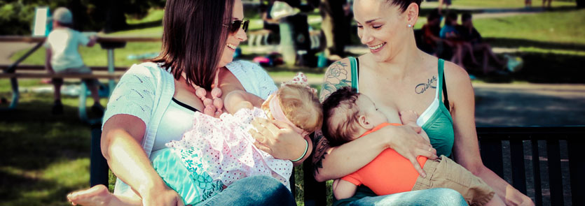 Two adults breastfeeding babies in a park with blurred people in the background.