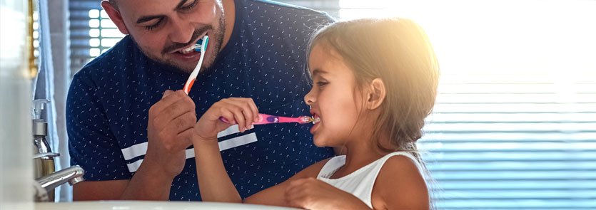 A dad and a daughter brushing their teeth at the sink in a bathroom