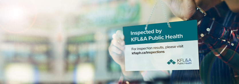 Business owner installing a KFL&A Public Health inspection sign