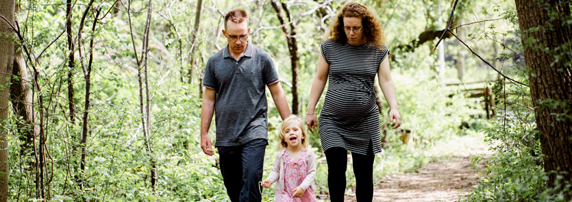 Two adults, one is pregnant, and child walking on a trail in the forest.