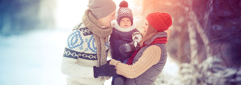 two adults holding a child outside in the winter