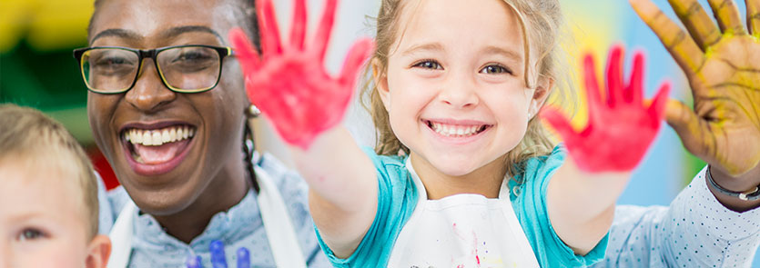 A child holding up their hands during a painting activity with a teacher