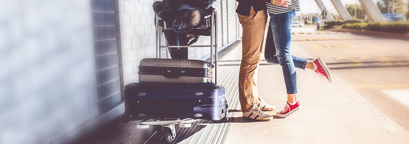 two people hugging beside luggage