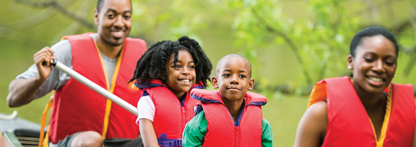 Two adults and two children wearing life jackets