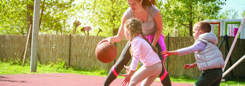 Adult and two children playing basketball