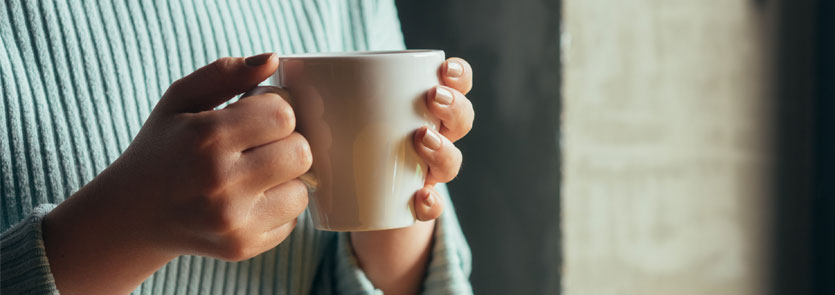 Adult hands holding a mug.