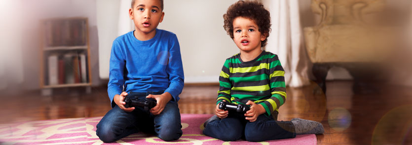 Children sitting on the floor playing video games
