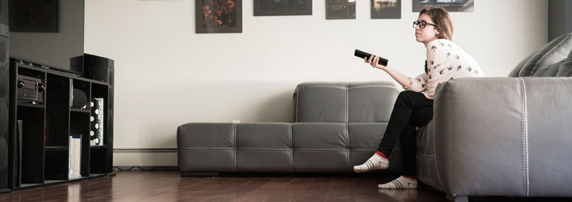 Teen sitting on the couch with a TV remote in hand