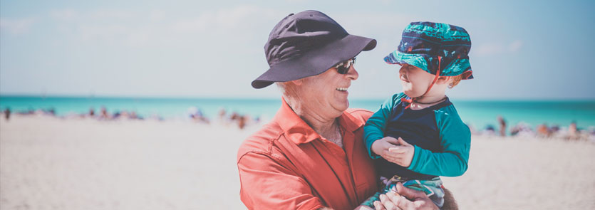 An older man holding a toddler on the beach