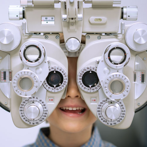 Child looking through eye exam machine.